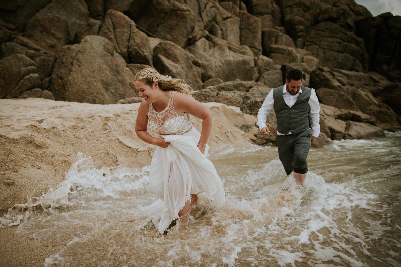 Wedding Couple has fun o a rough Beach in Cornwall